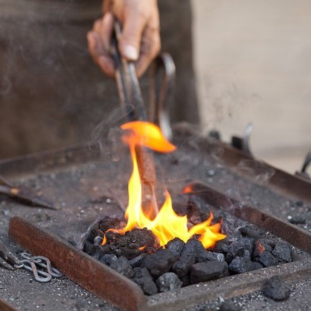 10694545 - embers, fire, smoke, tools and the hands of a blacksmith