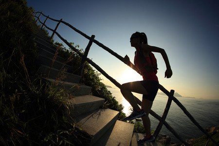 52522953 - young fitness woman trail runner running up on mountain stairs